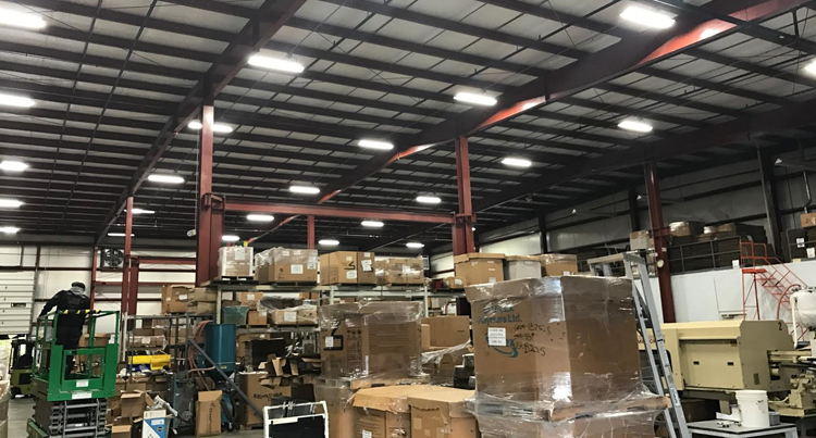 lighting retrofit job for warehouse, a warehouse lighting retrofit job, picture of a warehouse with a bunch of boxes piled up that has a lighting retrofit job